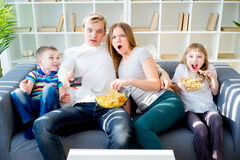 Family watching scary movie at home. Royalty Free Stock Images