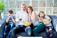Family watching scary movie at home. Stock Photo