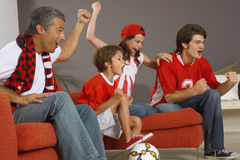 Family watching a sports match on TV. Family watching a football match on TV royalty free stock image