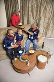Family watching sports on tv. Mother serving snacks to male African-American family members during football game stock photo