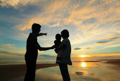 Family watching the sunrise on the beach stock photography