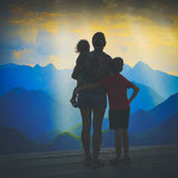 Family watching sunset above the valley. Instagram stylisation. Silhouette of family watching sunset above the mountain valley with beautiful rays of light in a Royalty Free Stock Photography