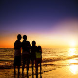 Family watching the sunset on the beach Stock Photos