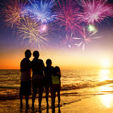 Family watching the sunset and firework on the beach Stock Photography