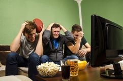 Family watching super bowl, near miss. Missed chance, father and sons holding head in despair royalty free stock photos