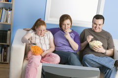 Family Watching Television. Happy obese family watching television together Royalty Free Stock Photography