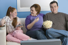 Family Watching Television. Happy obese family watching television together Stock Image