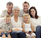 Family watching television and eating chips Royalty Free Stock Images