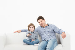 Family watching television sitting on sofa at home Stock Photo