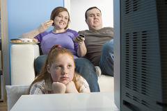 Family Watching Television Together. Obese family watching television together at home Royalty Free Stock Photo