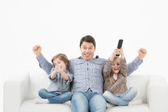 Family watching television together on the sofa Stock Photography