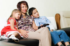 A family watching  a tv. A young mother with two kids, a boy and a girl, is sitting on a sofa and watching a tv Stock Images