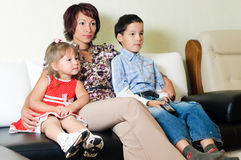 A family watching  a tv. A young mother with two kids, a boy and a girl, is sitting on a sofa and watching a tv Royalty Free Stock Photos