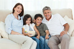 Family watching tv. While they are eating popcorn Royalty Free Stock Images