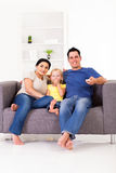 Family watching tv. Happy young family watching tv on sofa at home Stock Images