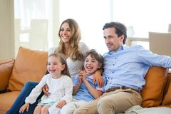 Family watching tv. Adorable family with two children watching tv in the living room and smiling Royalty Free Stock Image