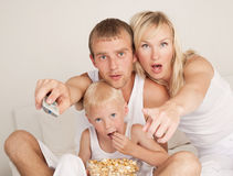 Family watching TV. Family: father, mother and son  relaxing, watching TV and eating popcorn in bed at home Royalty Free Stock Photo