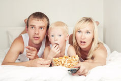 Family watching TV. Happy family: father, mother and son  relaxing, watching TV and eating popcorn in bed at home Royalty Free Stock Photo