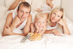 Family watching TV. Happy family: father, mother and son  relaxing, watching TV and eating popcorn in bed at home Royalty Free Stock Photography