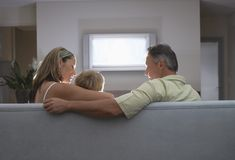 Family Watching TV At Home. Patents with son on sofa watching TV at home Royalty Free Stock Images