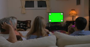 Family watching TV at home, chroma key stock video footage