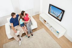 Family watching tv at home. High angle view of family watching TV together while relaxing on sofa at home Stock Photos