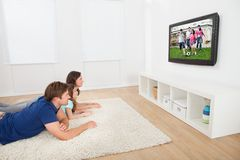 Family watching tv at home. Family of three watching TV while lying on rug at home Royalty Free Stock Image