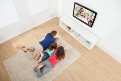 Family watching tv at home. Family of three watching TV while lying on rug at home Royalty Free Stock Photo