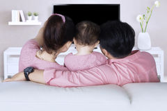 Family watching tv in living room. Back view of happy family watching tv while sitting on sofa in the living room Stock Photo
