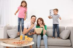 Family watching TV with popcorn royalty free stock images
