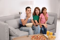 Family watching TV with popcorn royalty free stock photography