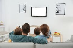 Family watching TV in room stock images