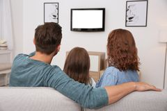 Family watching TV in room stock photos