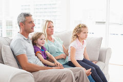 Family watching TV while sitting on sofa. Family of four watching TV while sitting on sofa at home Stock Image