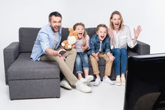 Family watching tv while sitting on sofa together Royalty Free Stock Image