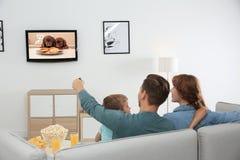 Family watching TV on sofa stock image