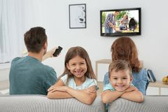 Family watching TV on sofa stock images