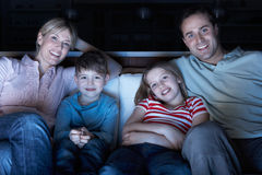Family Watching TV On Sofa Together Stock Photos