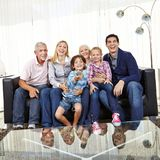 Family is watching TV together. Big happy family is watching TV together in the living room with remote control royalty free stock photos