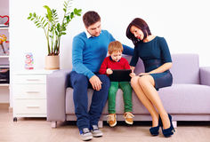 Family watching video on tablet, while sitting in waiting room Stock Photo