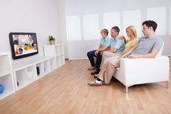 Family watching widescreen television. Family with teenage children sitting together on a sofa in the living room watching widescreen television Stock Photography