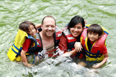 Family in the water. Cheerful family in the water wearing life vest smiling at camera stock image