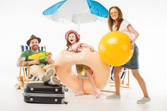 Family with water gun, flotation ring and ball royalty free stock photo