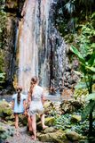 Family at waterfall. Back view family of mother and daughter enjoying view of Diamond waterfall on Saint Lucia island in Caribbean stock photo