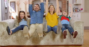 Family waving at camera on couch stock video