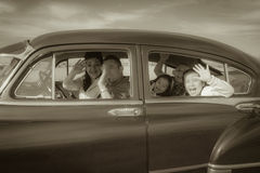 Family Waving Hello in Vintage Car Stock Image