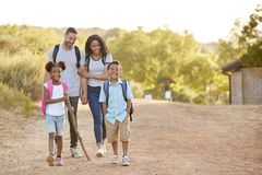 Family Wearing Backpacks Hiking In Countryside Together royalty free stock photography