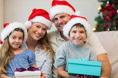 Family wearing Christmas hat while holding presents Royalty Free Stock Photography