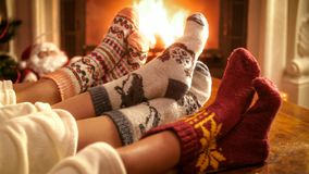 Family wearing knitted woolen socks warming feet at fireplace on Christmas eve. Family wearing woolen socks warming feet at fireplace on Christmas eve stock image