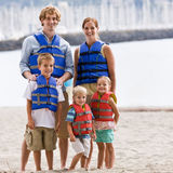 Family wearing life jackets at beach Royalty Free Stock Images